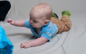 Reaching for toys while on the tummy strengthens back, neck and arm muscles.